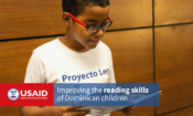 "A boy reads a book. The image has the USAID logo, and says ""Improving the reading skills of Dominican children"""