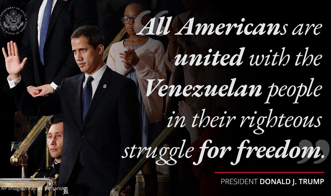 """Venezuela's interim President Juan Guaido waves. Text next to him says """"All Americans are united with the Venezuelan people in their righteous struggle for freedom."""""""
