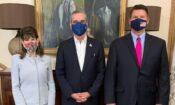 Una mujer y dos hombres de pie.
