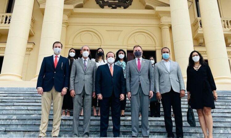 Enc de negocios y ministros junto a becarias en las escaleras de la entrada del Palacio Nacional