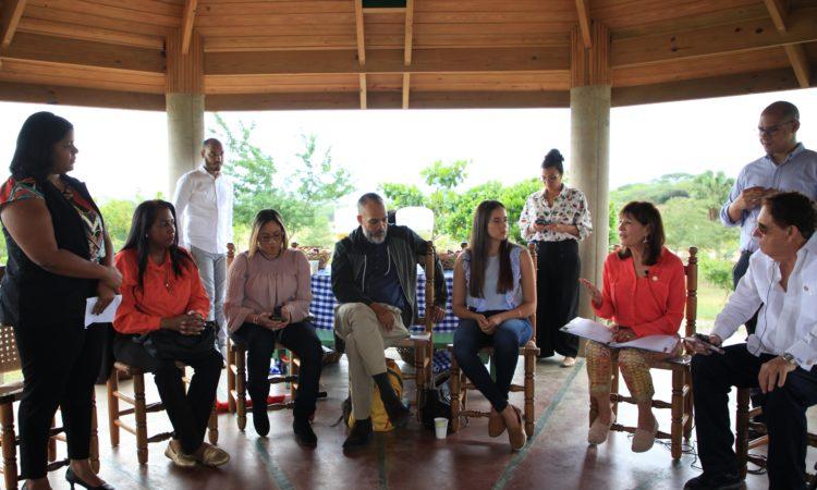 Una mujer está de pie, mientras otra, sentada, habla, y alrededor, sentados y de pie, hay otros hombres y mujeres.