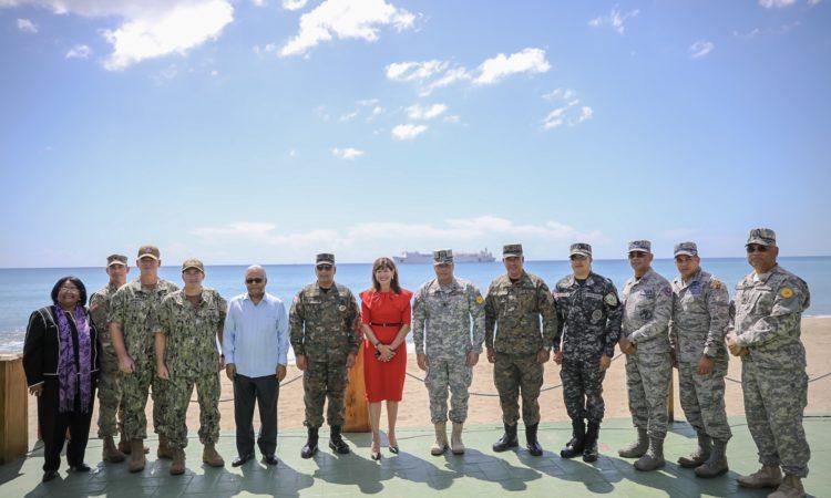Un grupo de personas, civiles y militares. Detrás de ellos el mar, y un buque.
