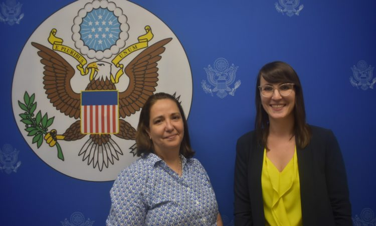 Two women smile in front of the Department of State seal