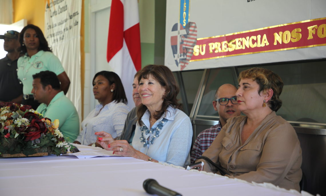 A woman smiles while sitting at a table, next to a man and other women. Behind her, a Dominican flag.
