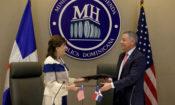 Un hombre y una mujer intercambian documentos. Detrás de ellos, una bandera estadounidense y una dominicana.