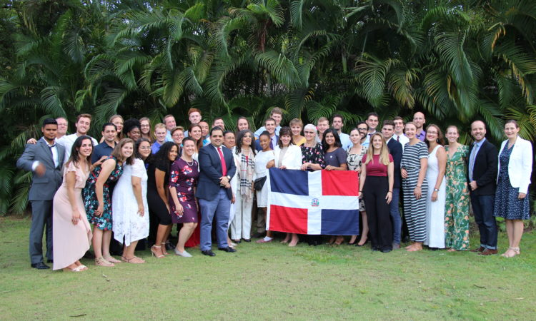 La embajadora sostiene una bandera dominicana junto con los nuevos voluntarios.
