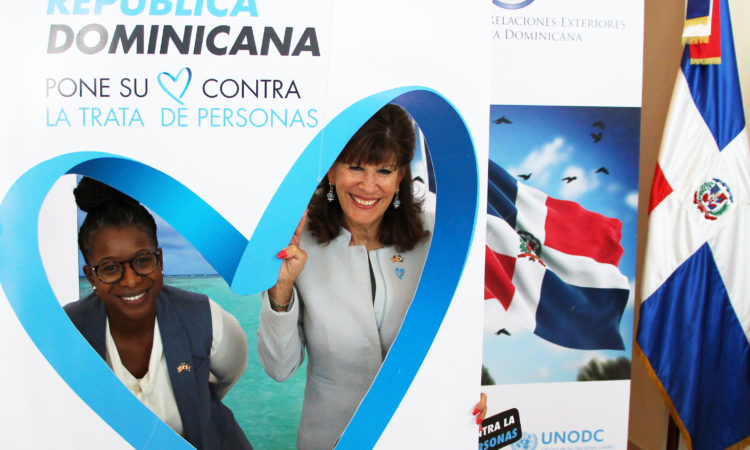Two women smile inside a figure of a blue heart. Next to them, a photo of a Dominican flag.
