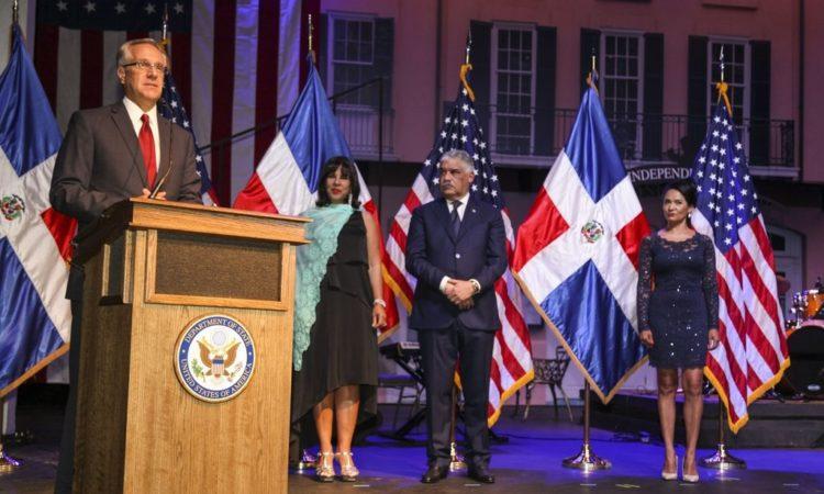 Un hombre parado en un podio junto a tres otras personas en un escenario.