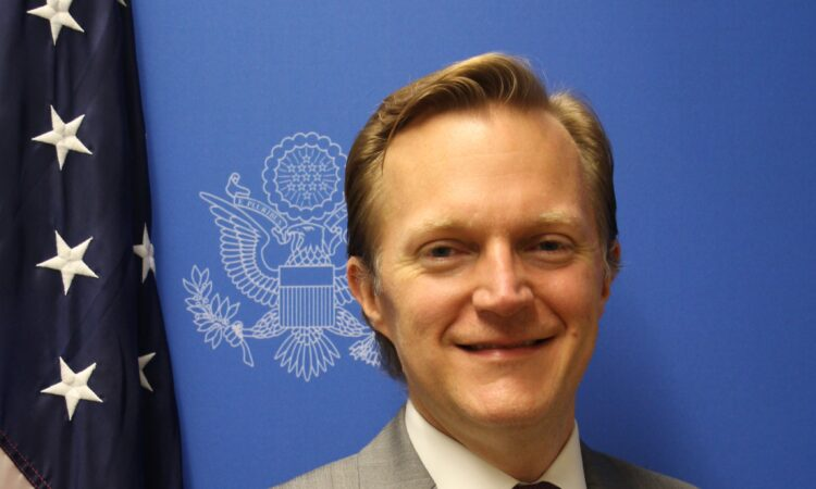 A man smiling, with the Department of State Seal and the U.S. flag behind him.