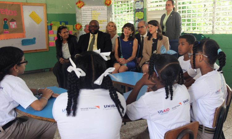 A group of elementary school girls and boys speak to men and women in a classroom