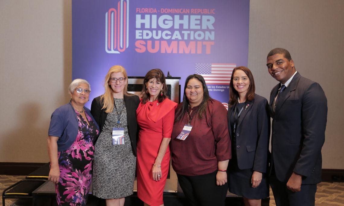 """Cinco mujeres y un hombre sonríen. Detrás de ellos, un panel que dice """"Florida-Dominican Republic Higher Education Summit"""""""