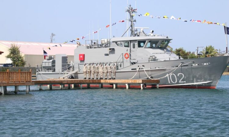 Un barco militar en un muelle, y varios oficiales militares parados dando la espalda al barco.