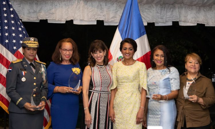 Six women, some of whom are holding awards, smile on a stage. Behind them, the flags of the United States and the Dominican Republic.