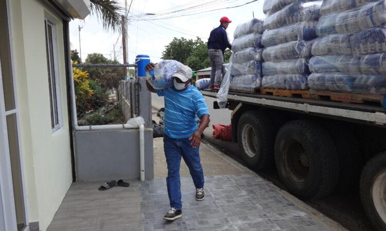 hombre caminando con alimentos al lado de un camión con estas provisiones