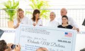 Dos mujeres, dos hombres y una adolescente sostienen un gran cheque que indica la cantidad de ochenta mil dólares.