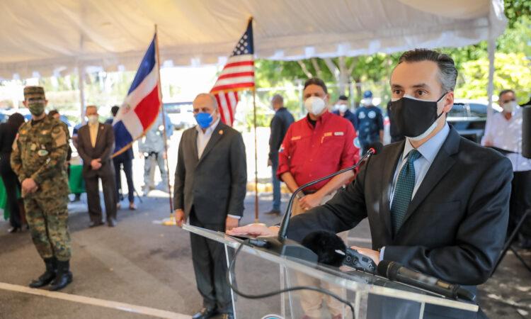 Un hombre hablando desde un podio. Detrás, otros hombres de pie y en el fondo las banderas dominicana y estadounidense.