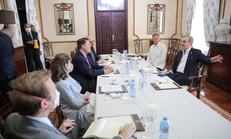 Un grupo de personas sentados en una mesa conversando.