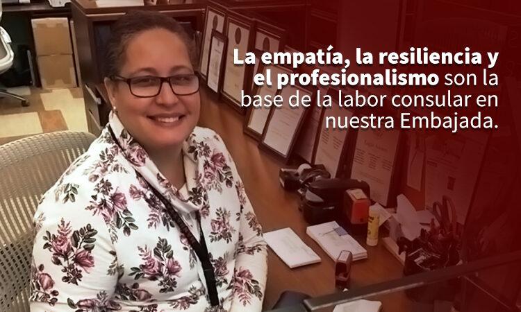 """Una mujer sonríe sentada en un escritorio. Hay un texto que dice """"la empatía, la resiliencia y el profesionalismo son la base de la labor consular de nuestra Embajada."""