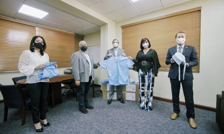 Cinco personas de pie en una oficina, sosteniendo indumentaria médica.