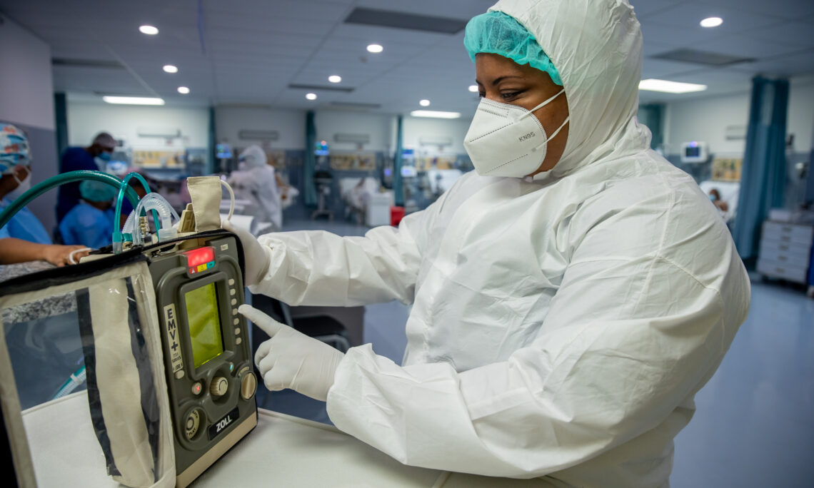 A healthcare worker works with a ventilator.