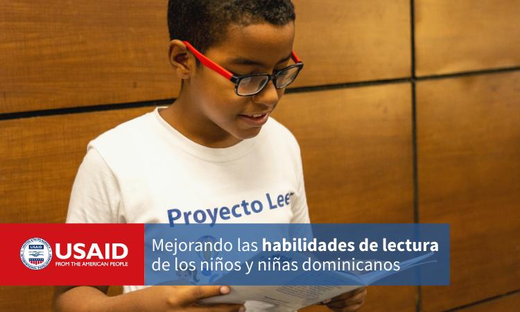 """Un niño lee un libro. La imagen incluye el logo de la USAID y dice """"Mejorando las habilidades de lectura de los niños y niñas dominicanos"""""""