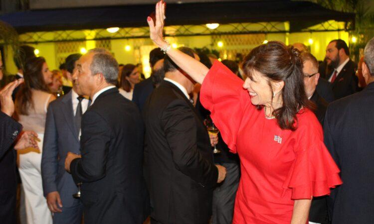 A woman next to a crowd, wearing a dress, waving.