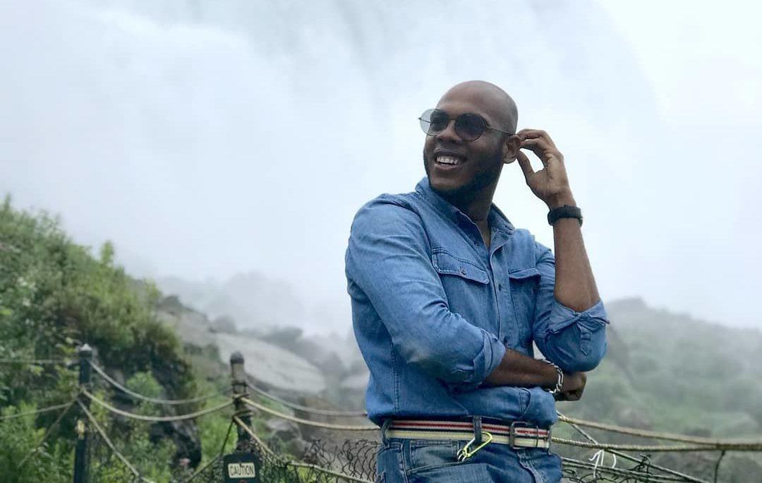 Un hombre sonriendo y mirando a su lado, con una montaña detrás.