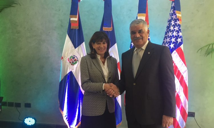 A woman and a man shake hands. Behind them two Dominican flags and two American flags.