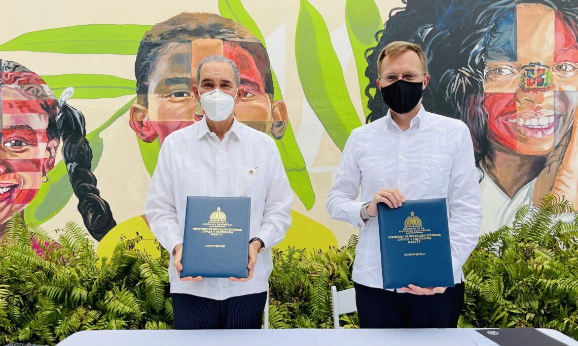 robert thomas y ministro de mescyt sosteniendo acuerdos firmados frente a mural del Dominico-Americano
