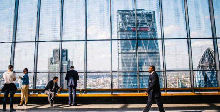 People walking by glass window