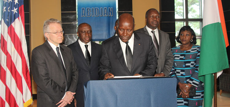 Ivoirian Prime Minister Daniel Kablan Duncan signing the condolence book with Ambassador McCulley