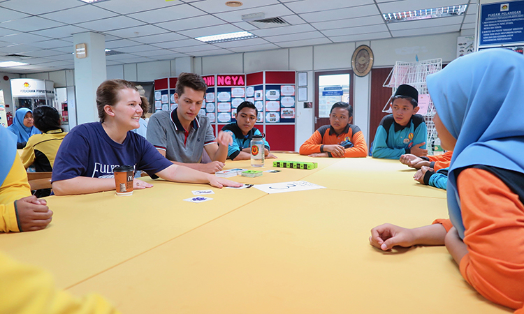 Fulbright ETAs lead a game of cards during the Lincoln Corner Kedah's 10th Anniversary celebration. (U.S. Embassy photo)