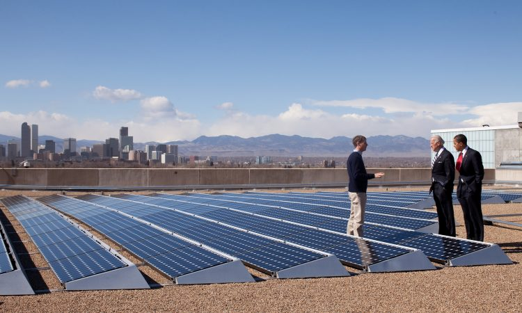 Men standing next to solar panels