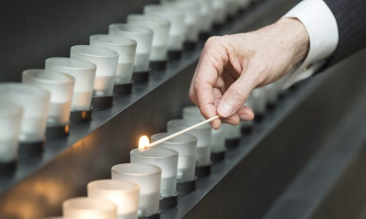 A man lights a memorial candle during an International Holocaust Remembrance Day commemoration at the United States Holocaust Memorial Museum in Washington. (© Saul Loeb/AFP/Getty Images)