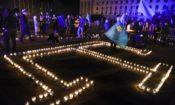 Молодые крымские татары с голубыми флагами крымских татар зажигают свечи в форме их крымскотатарского символа во время митинга панихиды 15 мая 2015 года в Симферополе.