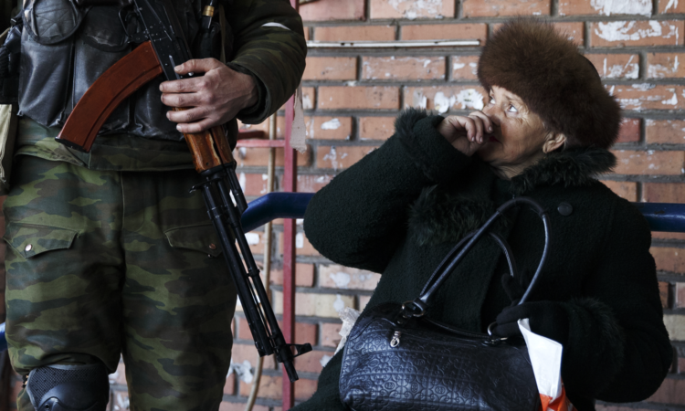 A woman looks at a Russia-backed separatist in Debaltseve, Ukraine, Feb. 23, 2015. (AP Photo/Vadim Ghirda)