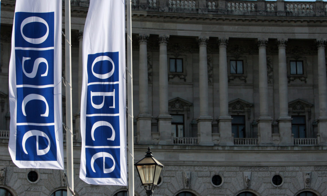 Flags with the OSCE logo in Russian and English in front of the Hofburg in Vienna. (OSCE/Mikhail Evstafiev)