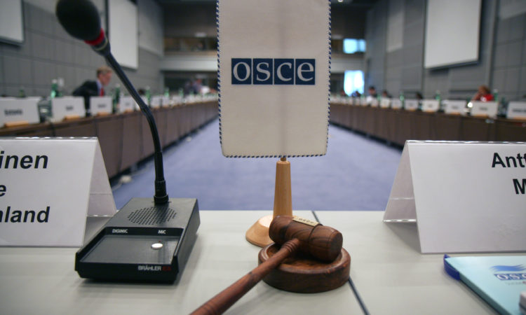 An OSCE flag and a gavel before the start of a meeting at the Hofburg in Vienna. (OSCE/Mikhail Evstafiev)