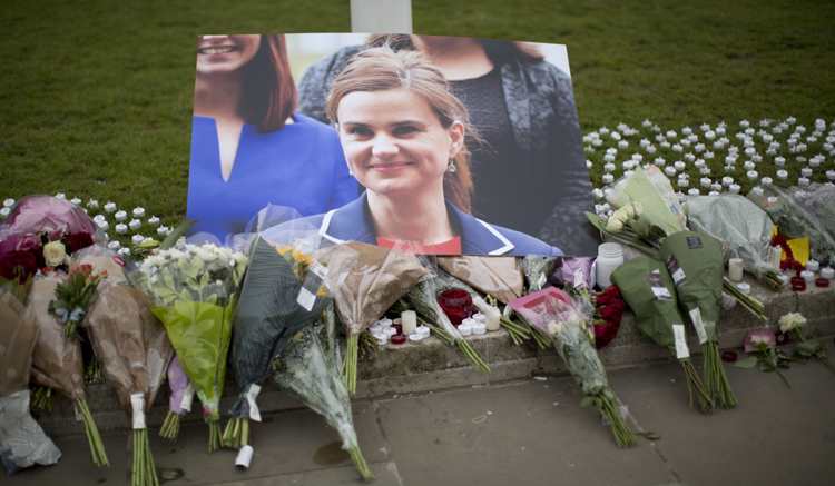 An image and floral tributes for Jo Cox, lay on Parliament Square, outside the House of Parliament in London, Friday, June 17, 2016. (AP)