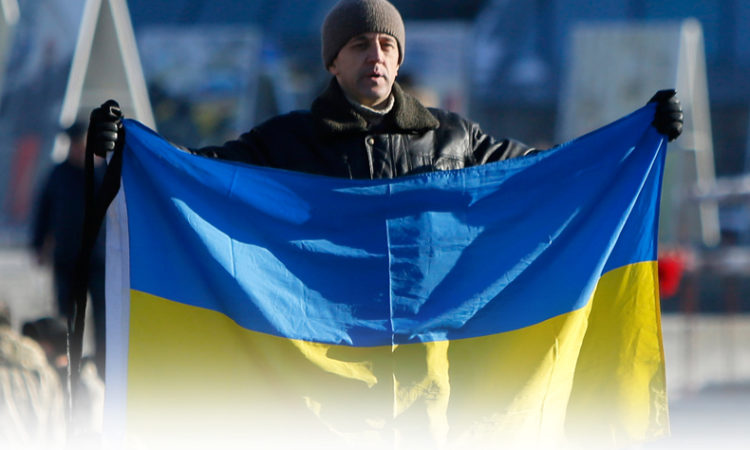 Мужчина, державший украинский флаг на Майдане Незалежности в Киеве, Украина, 18 февраля 2015 года. (AP Photo/Sergei Chuzavkov)