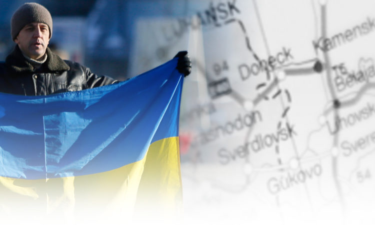 Man holds Ukrainian flag over map of eastern Ukraine