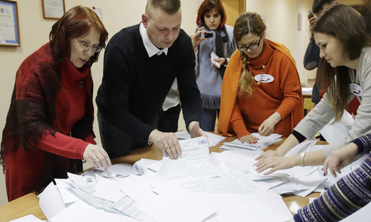 Members of the local election commission count ballots at a polling station during the presidential election in St.Petersburg, Russia, Sunday, March 18, 2018. (AP Photo/Dmitri Lovetsky)
