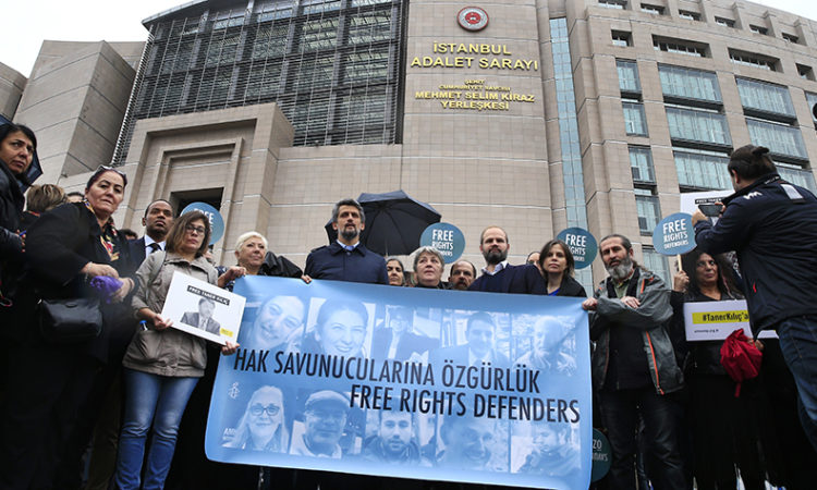 Human rights activists stage a protest outside a court in Istanbul. (AP Photo/Lefteris Pitarakis)