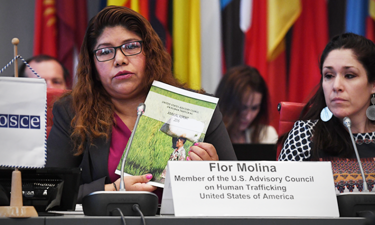 Flor Molina, a human trafficking survivor and member of the U.S. Advisory Council on Human Trafficking, holds up a copy of the Council's 2016 Annual Report during her presentation at a session of the 18th Alliance Against Trafficking in Persons Conference, Vienna, Austria, April 24, 2018. (USOSCE/Colin Peters)