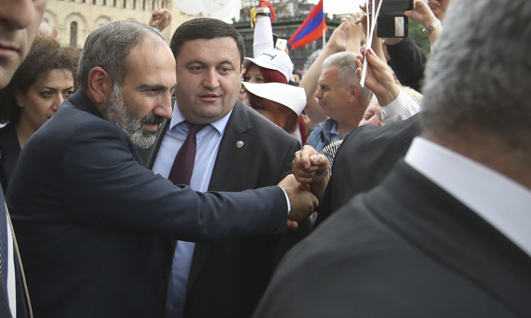 Prime Minister of Armenia Nikol Pashinian, left, is greeted by supporters in Republic Square in Yerevan, Armenia, Tuesday, May 8, 2018. (AP Photo/Thanassis Stavrakis)
