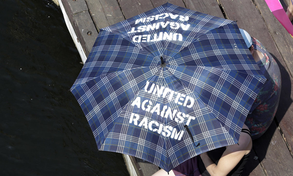 A woman with an umbrella protesting against racism, May, 2018. (AP Photo)