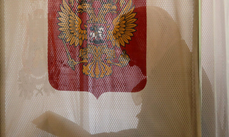 A woman fills her ballots at a polling station in the village of Gusino, outside Smolensk, western Russia. (AP Photo/Sergei Grits)