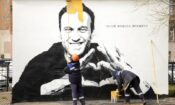 """Municipal workers paint over graffiti of Russia's imprisoned opposition leader Alexei Navalny in St. Petersburg, Russia, Wednesday, April 28, 2021. The worlds on the wall reading """"Hero of our time"""". (AP Photo/Ivan Petrov)"""