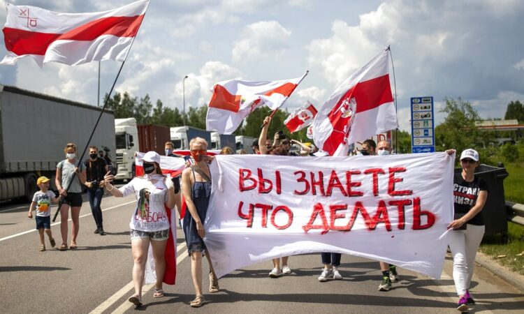 """Protesters hold a banner reading """"You know what to do"""" , and old Belarusian national flags during a protest demanding freedom for political prisoners in Belarus near Medininkai, Lithuanian-Belarusian border crossing east of Vilnius, Lithuania, Tuesday, June 8, 2021. (AP Photo/Mindaugas Kulbis)"""