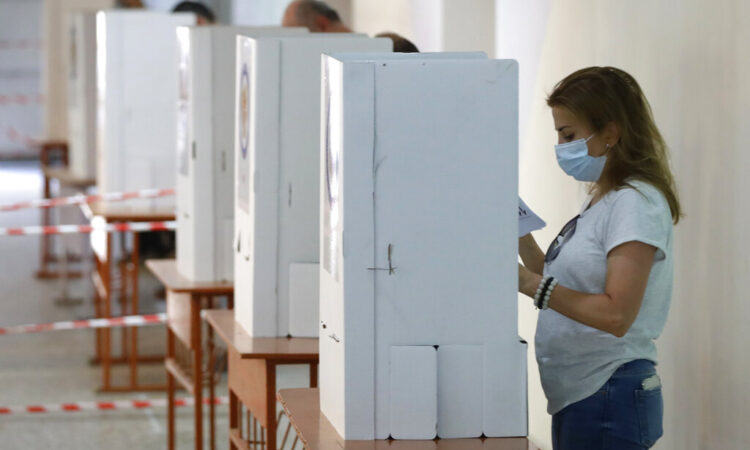 People read their ballot papers at a polling station during a parliamentary election in Yerevan, Armenia, Sunday, June 20, 2021. (AP Photo/Sergei Grits)